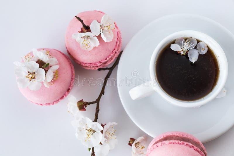 Taza de café con los macarons rosados y las flores blancas imágenes de archivo libres de regalías