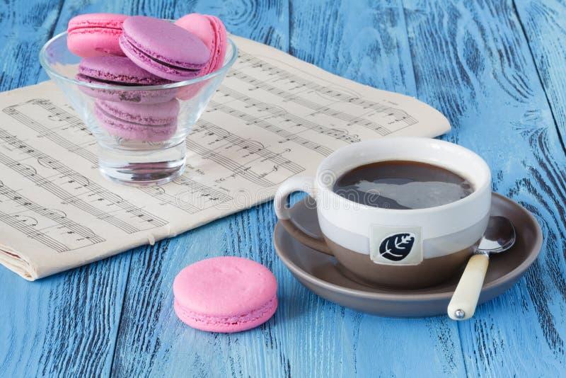 Taza de café con los macarrones y las notas musicales en fondo fotos de archivo libres de regalías