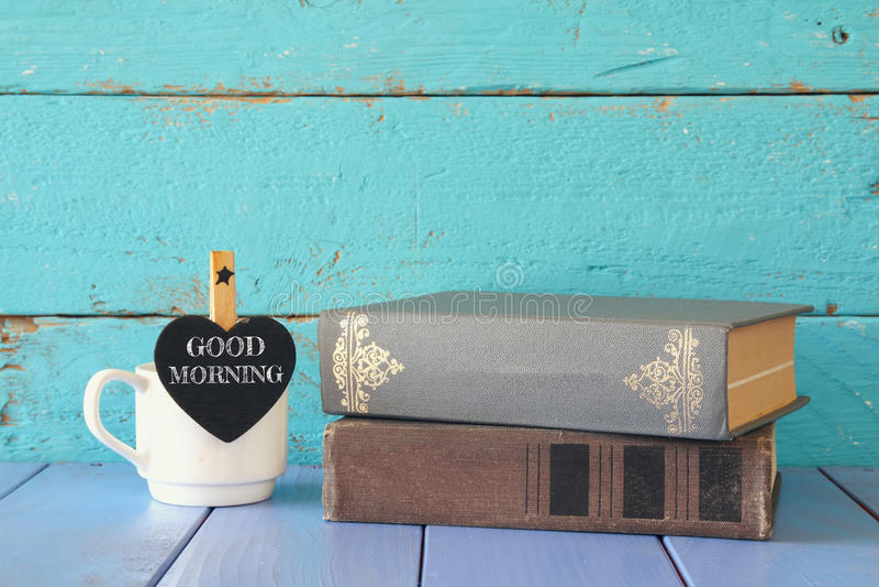 Taza de café con una poca pizarra de la forma del corazón con la frase: BUENA MAÑANA al lado de la pila de libros viejos foto de archivo