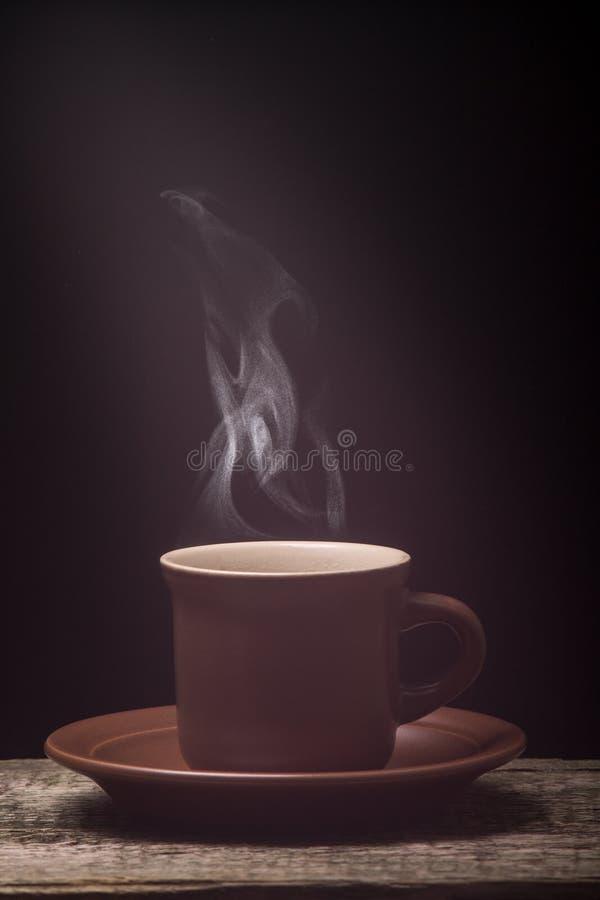 Taza de café con vapor en el tablero de madera Fondo negro imagen de archivo