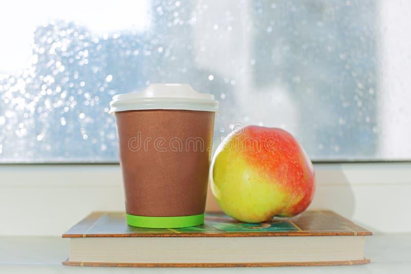 Taza de café contra ventana con día lluvioso imagen de archivo