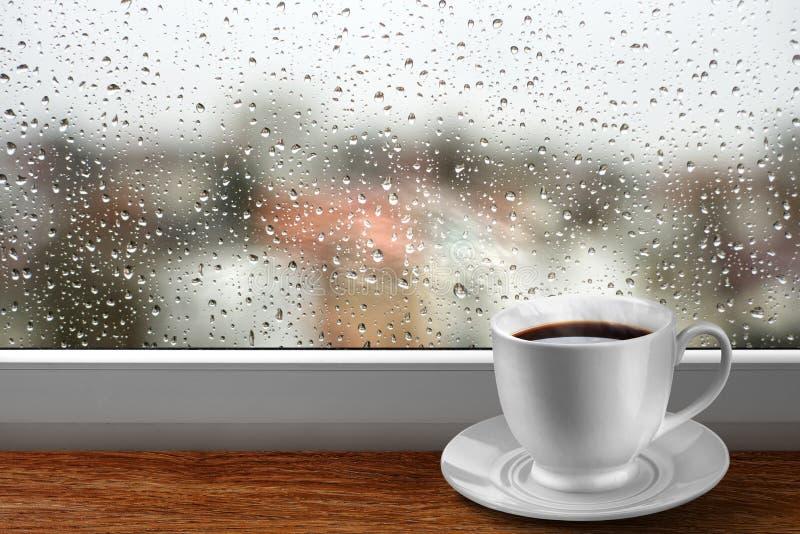Taza de café contra ventana con la opinión de día lluvioso fotos de archivo