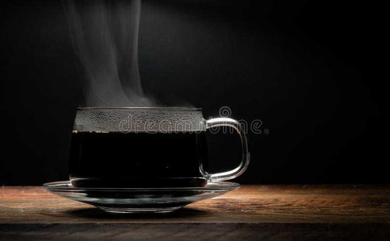 Taza de café de cristal del Lit superior en fondo negro foto de archivo