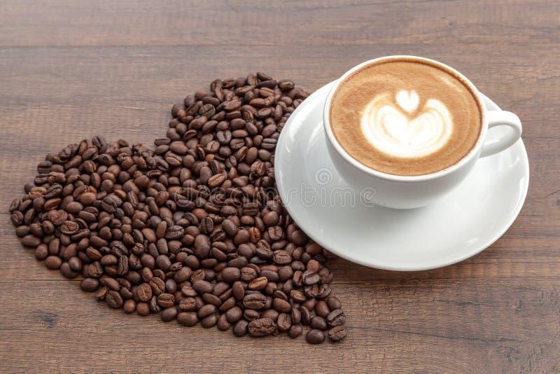 Taza de café de arte del latte con los granos de café en forma del corazón en la madera imagen de archivo libre de regalías