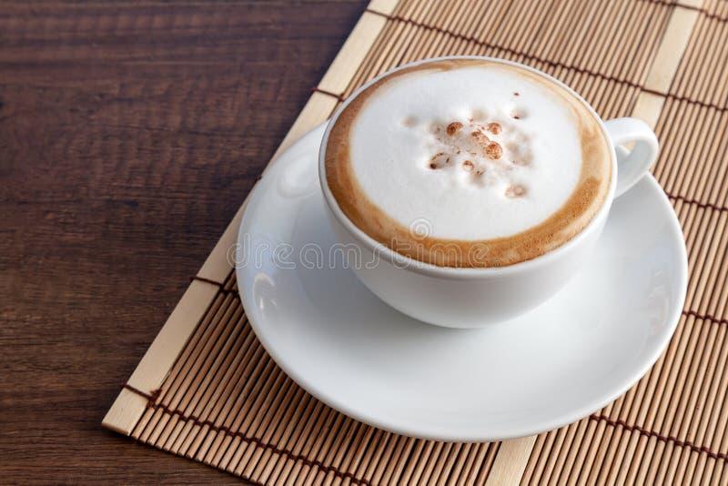 Taza de café de capuchino en la estera de bambú, en ingenio de madera del fondo foto de archivo