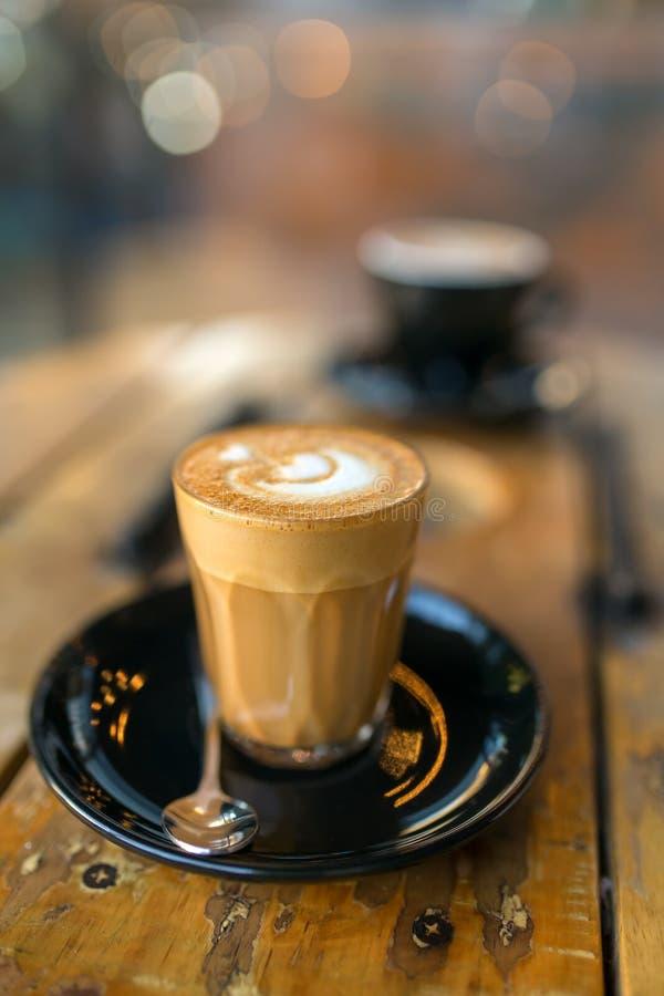 Taza de café de flautín caliente del latte en el primer de madera rústico de la tabla foto de archivo