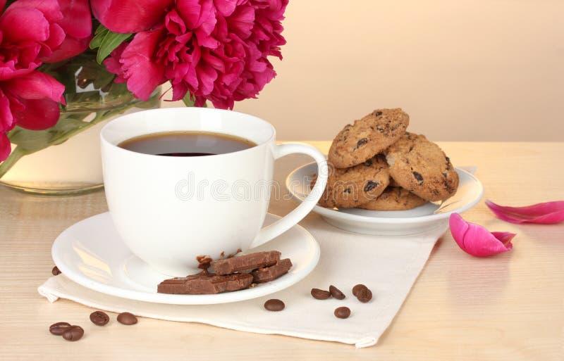 Taza de café, de galletas, de chocolate y de flores foto de archivo libre de regalías