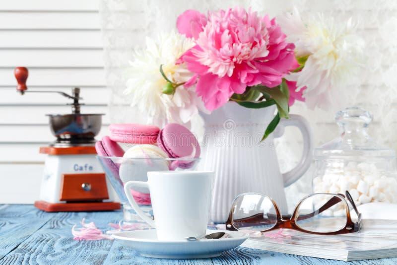 Taza de café, de galletas y de flores en la tabla imagen de archivo