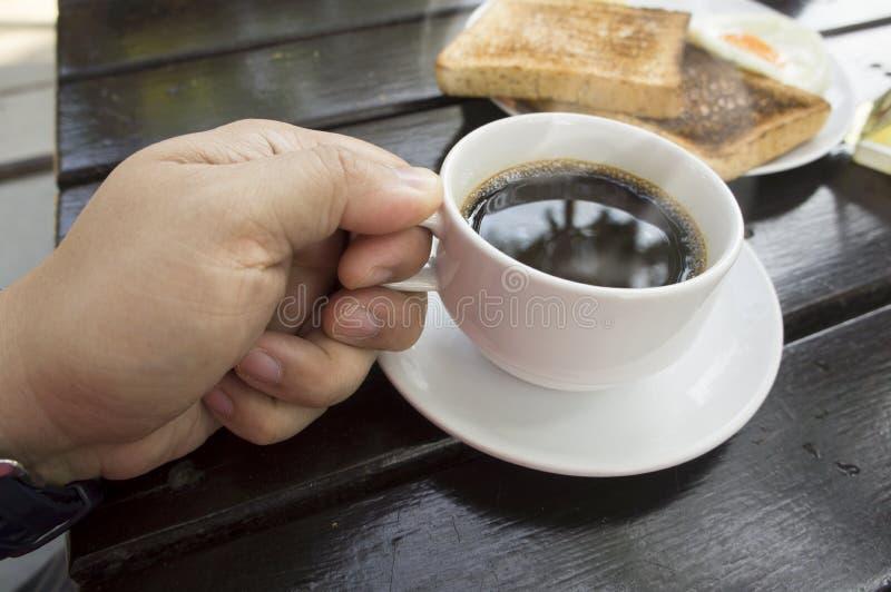 Taza de café de la elevación de la mano imagen de archivo