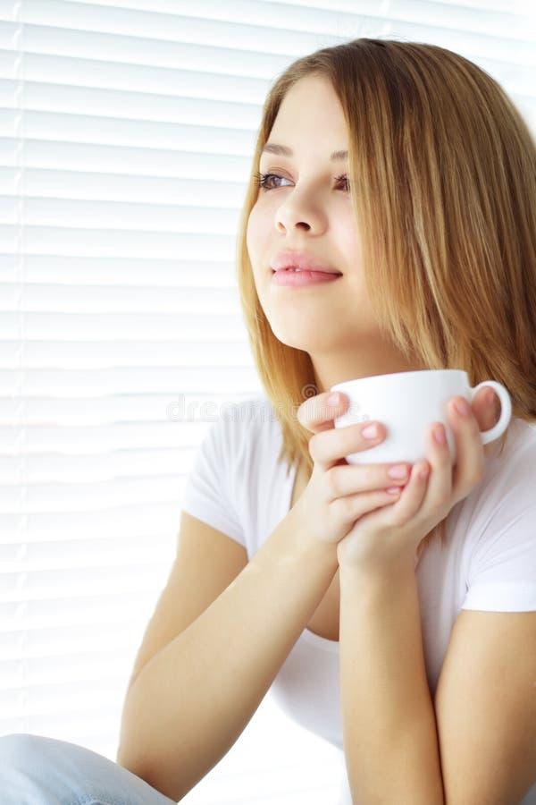 Taza de café de la explotación agrícola de la muchacha foto de archivo libre de regalías