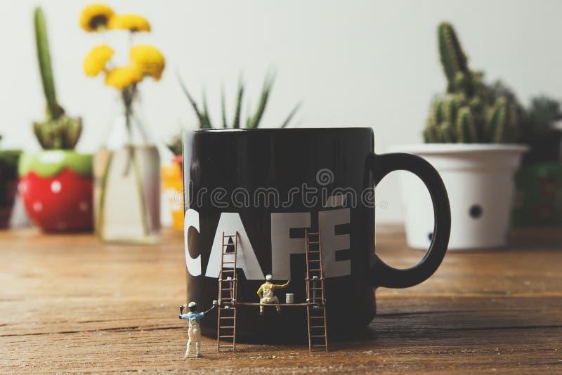 Taza de café de pintura de la gente miniatura fotografía de archivo libre de regalías