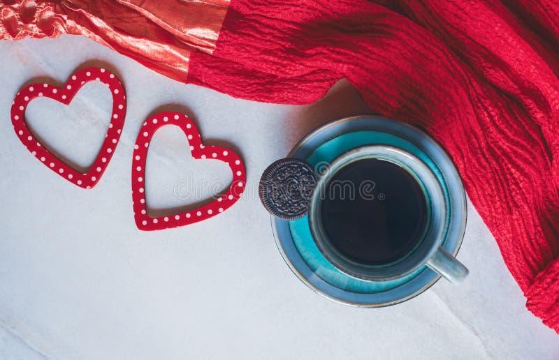 Taza de café, de decoraciones de los corazones y de una bufanda roja en el fondo blanco foto de archivo