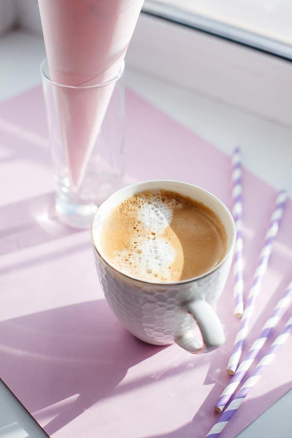 Taza de café del americano en alféizar en la pieza de una rutina de la mañana, concepto mínimo del rayo del sol foto de archivo
