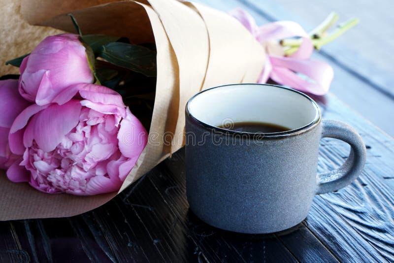 Taza de café del americano y de flores rosadas de las peonías imágenes de archivo libres de regalías