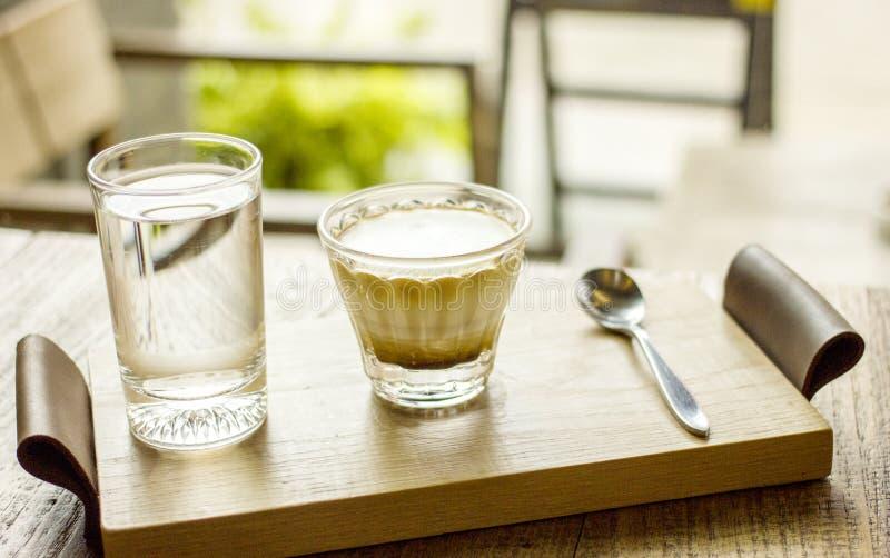 Taza de café del capuchino con el vidrio de la porción del agua en la bandeja de madera foto de archivo libre de regalías