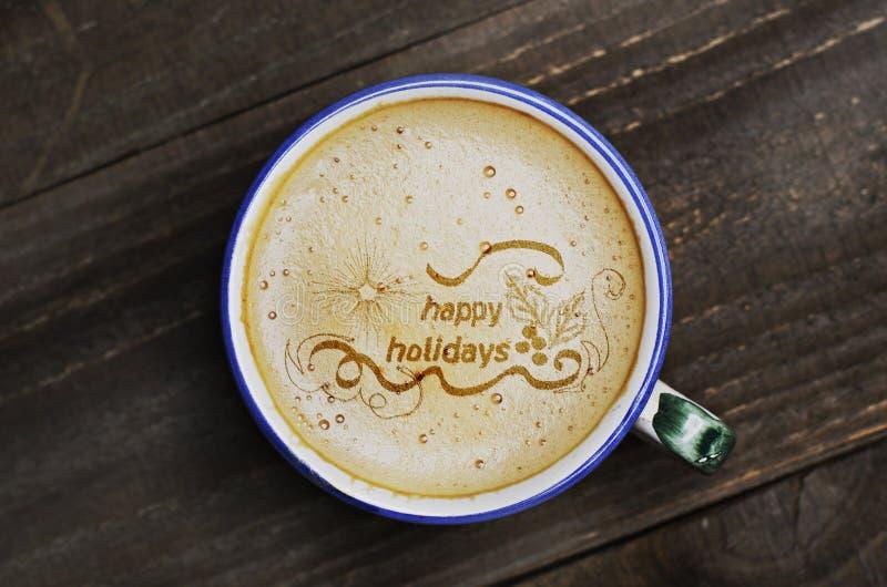 Taza de café del capuchino en la tabla de madera Palabras buenas fiestas f imágenes de archivo libres de regalías