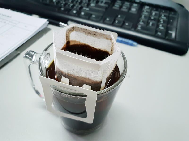 Taza de café del goteo con el teclado y el cuaderno fotos de archivo