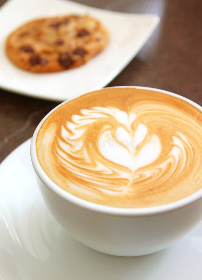 Taza de café del latte o del capuchino con la galleta foto de archivo libre de regalías