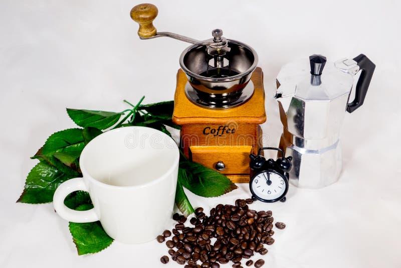 Taza de café, despertador, amoladora de café y caldera imagen de archivo