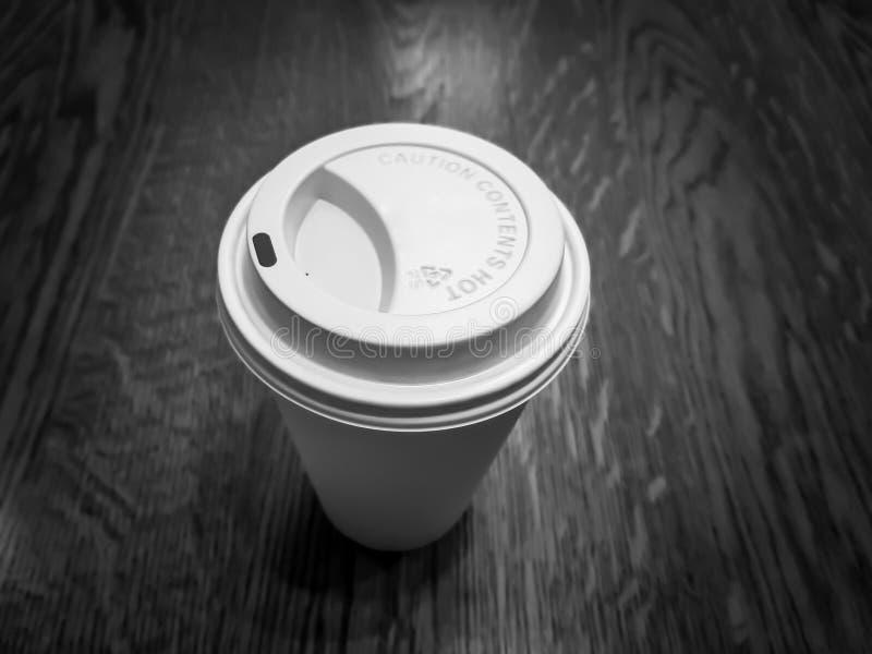 Taza de café disponible hecha del plástico y del papel, en una superficie de sobremesa de madera fotografía de archivo libre de regalías