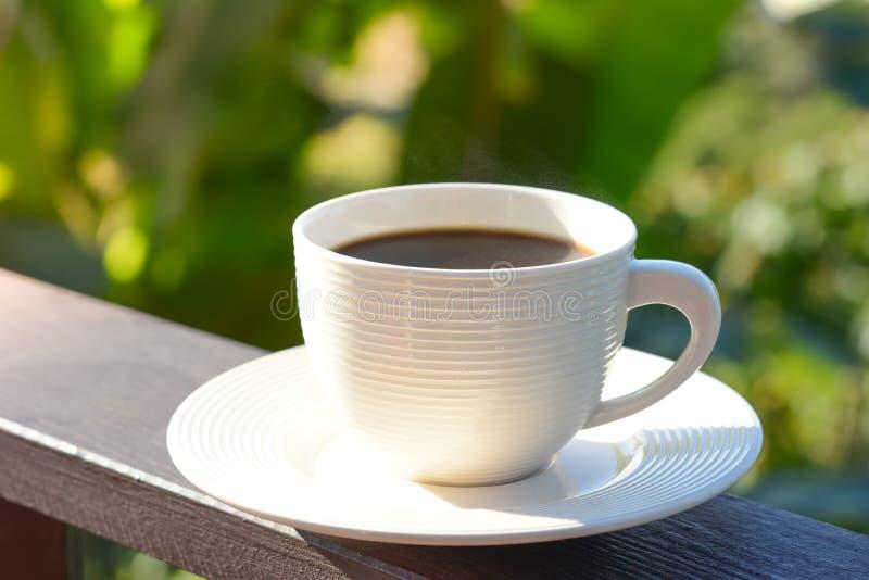 Taza de café en el carril de madera del balcón en fondo natural del verde de la falta de definición imagen de archivo