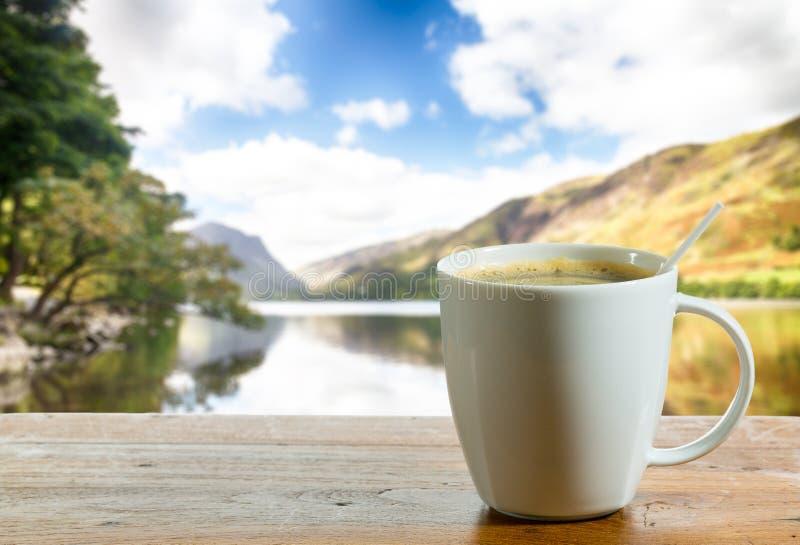 Taza de café en el vector de madera por el lago imágenes de archivo libres de regalías