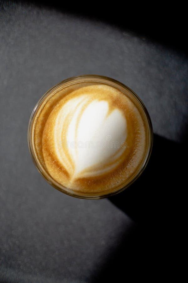 Taza de café en fondo negro con arte hermoso del latte fotografía de archivo libre de regalías