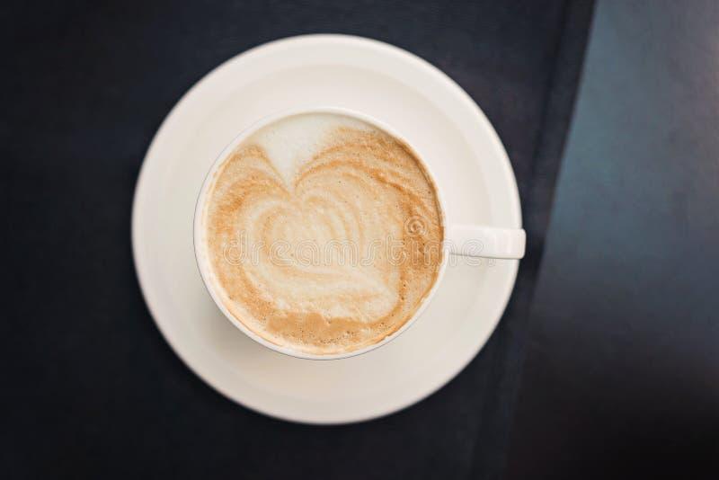 Taza de café en fondo negro de la tabla con el arte hermoso del latte en forma de corazón fotografía de archivo