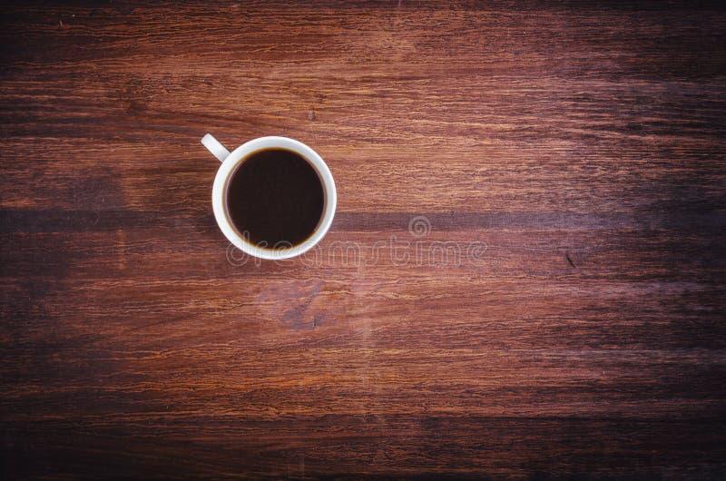 Taza de café en la opinión de sobremesa de madera del marrón oscuro imagen de archivo libre de regalías