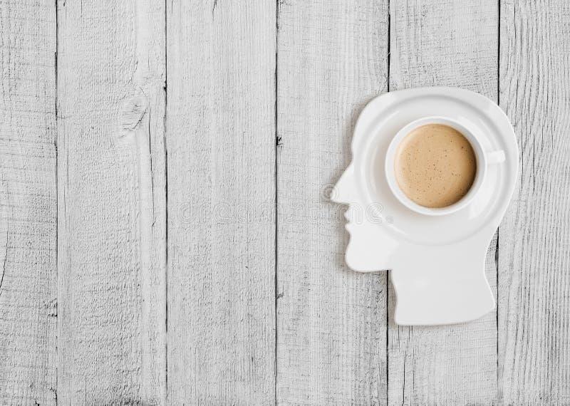 Taza de café en la placa en forma principal humana foto de archivo libre de regalías