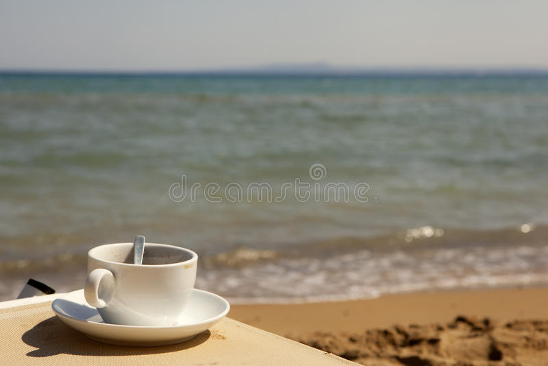Taza de café en la playa fotografía de archivo