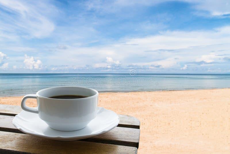 Taza de café en la playa fotos de archivo