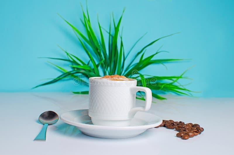 Taza de café en la tabla con las habas fotos de archivo