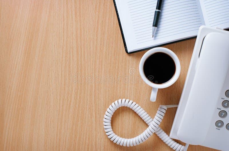 Taza de café en la tabla de telefonista imagen de archivo libre de regalías