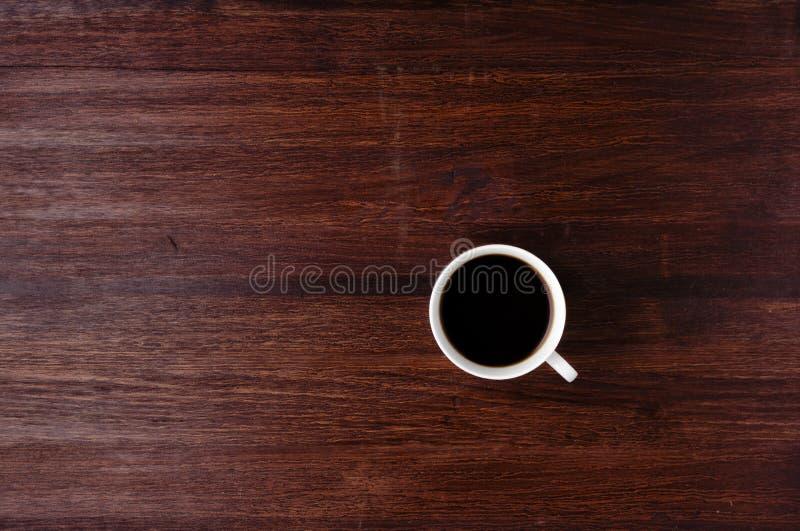Taza de café en la tabla oscura fotografía de archivo libre de regalías