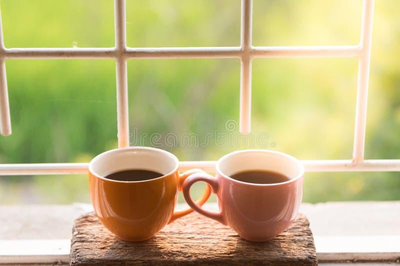 Taza de café en la ventana en la mañana con la naturaleza hermosa foto de archivo