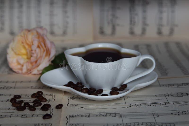 Taza de café en las hojas musicales con una rosa imágenes de archivo libres de regalías