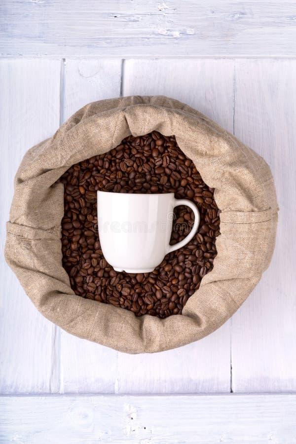 Taza de café en un bolso por completo de los granos de café imagen de archivo libre de regalías