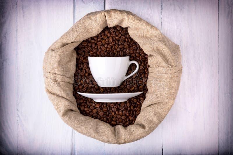 Taza de café en un bolso por completo de los granos de café imagenes de archivo