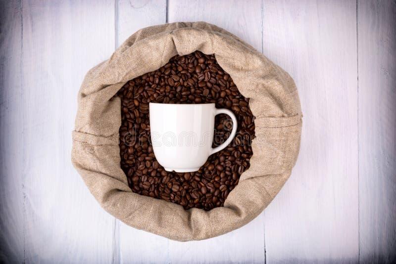Taza de café en un bolso por completo de los granos de café fotografía de archivo libre de regalías