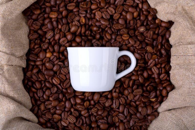 Taza de café en un bolso por completo de los granos de café foto de archivo