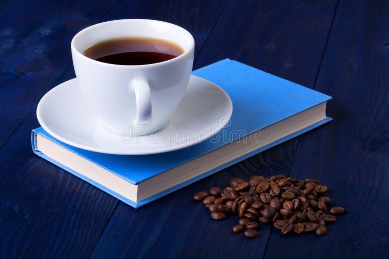 Taza de café en un libro azul foto de archivo libre de regalías