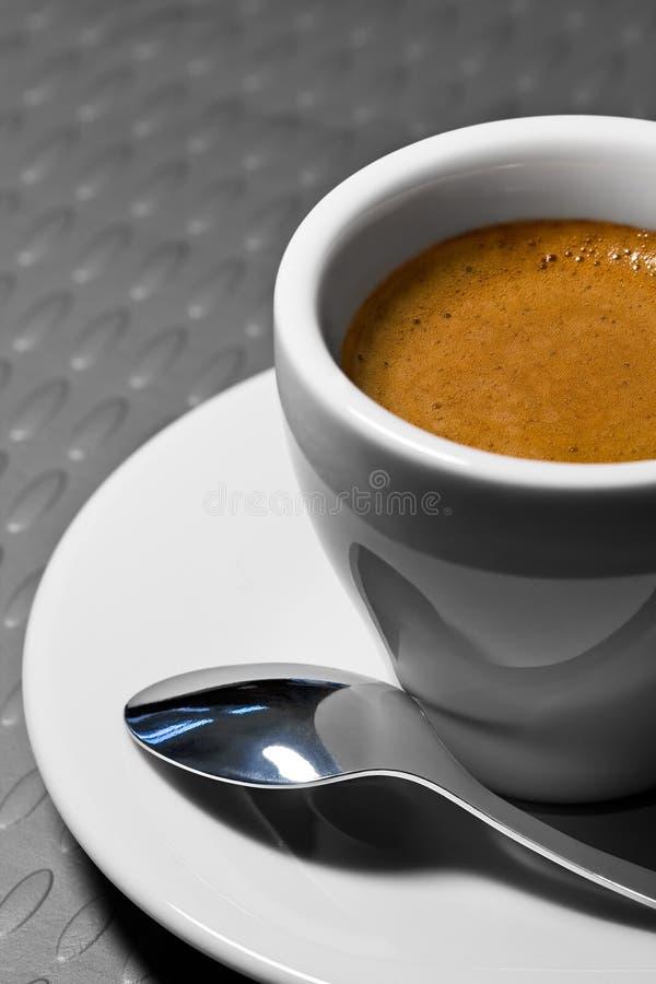 Taza de café en un platillo con la cuchara fotografía de archivo libre de regalías