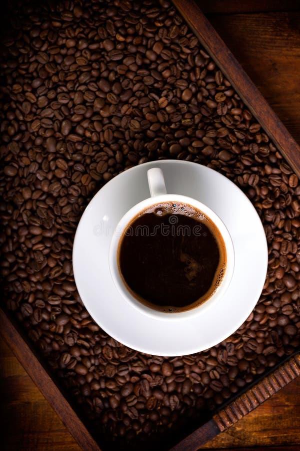 Taza de café en una bandeja por completo de habas imagenes de archivo