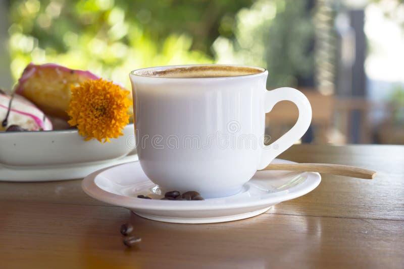 Taza de café en una tabla de madera imagen de archivo