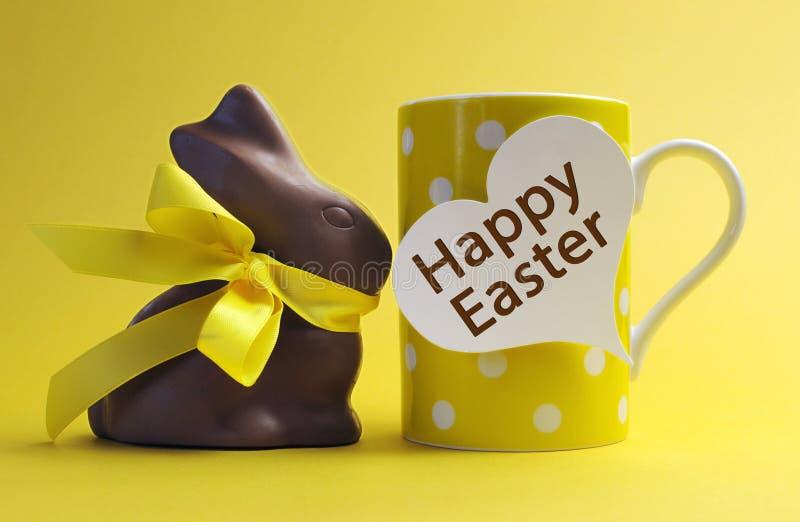 Taza de café feliz del desayuno del lunar de Pascua del tema amarillo con el conejo de conejito del chocolate fotografía de archivo libre de regalías
