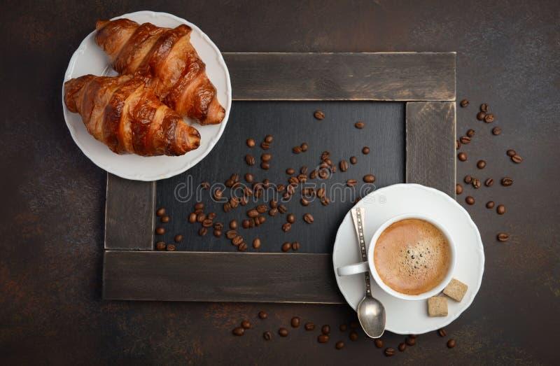 Taza de café fresco con los cruasanes en fondo oscuro imagenes de archivo