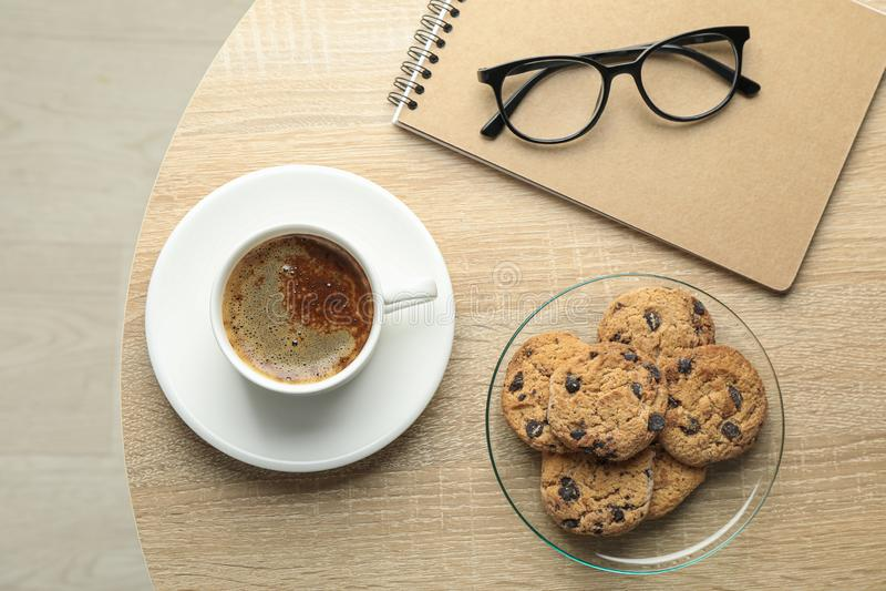 Taza de caf?, galletas, cuaderno y vidrios en la tabla de madera, visi?n superior y espacio para el texto foto de archivo