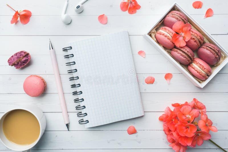 Taza de café, de galletas de los macarrones en una caja, de flores y de un cuaderno en un fondo blanco Copie el espacio desayuno  imagenes de archivo