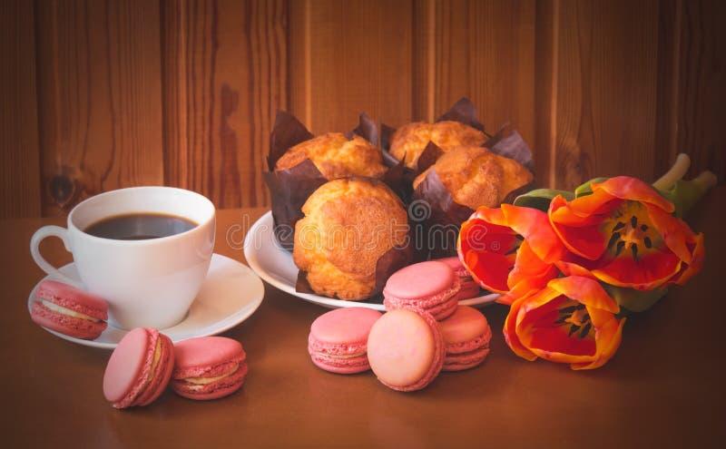 Taza de café, de galletas de los macarrones, de flores del tulipán y de molletes de la vainilla imagenes de archivo